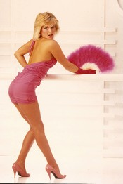 Vicky in a pink dress with a feather fan.